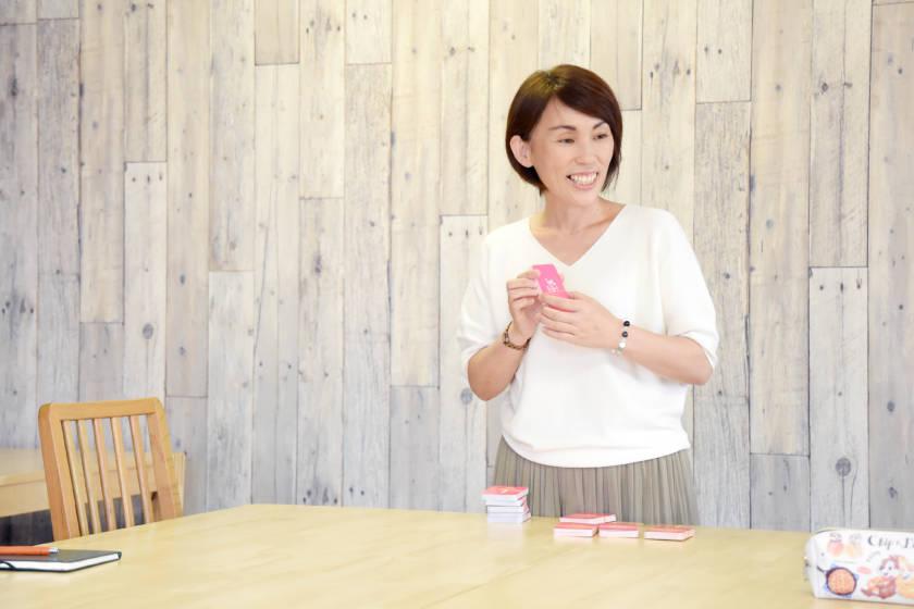 写真:カードを持った笑顔の女性